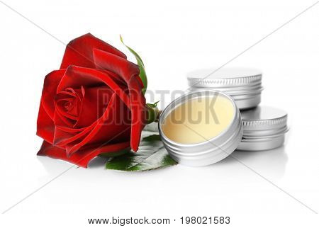 Containers with dry perfume and rose on white background
