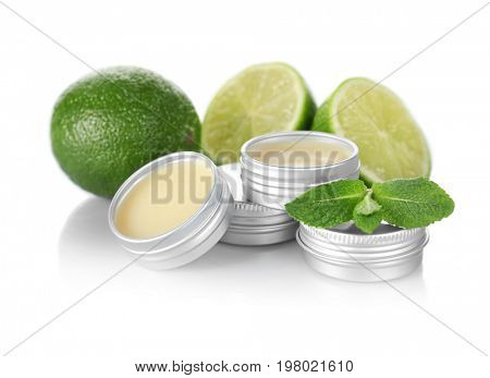 Containers with dry perfume, leaves of mint and lime on white background