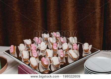 Eclairs traditional french dessert. candybar on a glass table