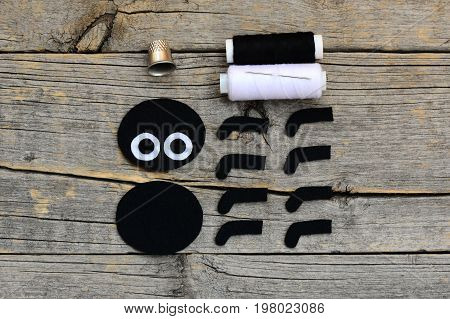 Making a Halloween felt spider decoration. Step. Cut black and white felt details to create Halloween toy. Sewing supplies on a wooden table. Halloween spider decor guide for kids. Top view