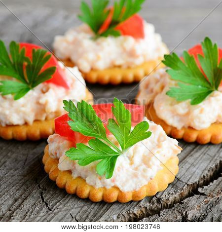 Simple small sandwiches with cream cheese on a wooden background. Quick snack from salted biscuits, spicy cream cheese, fresh tomato and parsley. Delicious appetizer idea. Closeup