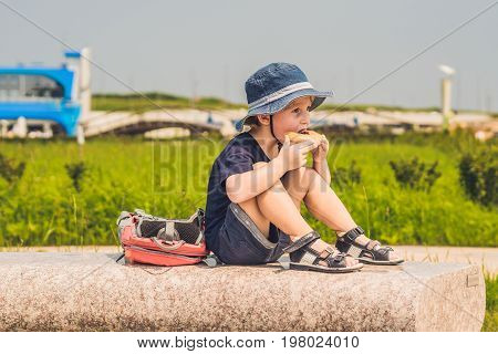 A Boy Eats His Snack On A Park Bench
