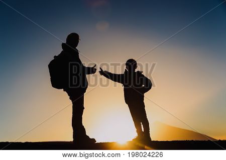family travel- father and son with backpacks hiking at sunset