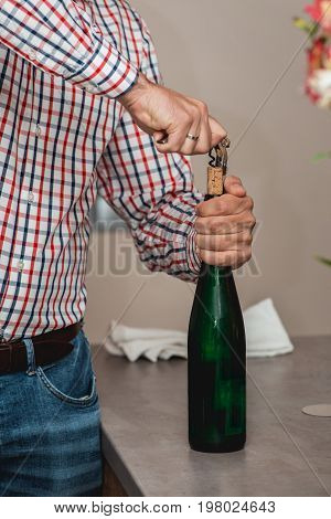 Sommelier Opening a wine bottle with corkscrew in a restaraunt