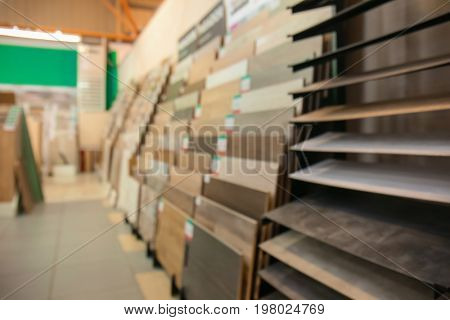 Assortment of laminated flooring samples in hardware store, blurred background