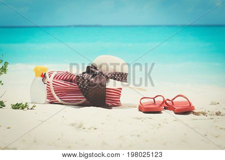 Beach bag, hat, slippers and suncream on tropical beach