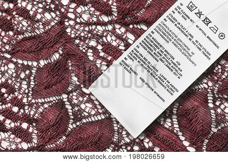 Washing instructions label on red lace as a background