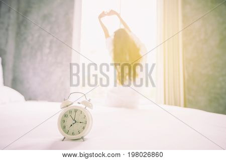 alarm clock having a good day of Asian woman waking up in her bed fully rested and open the curtains in the morning to get fresh air.