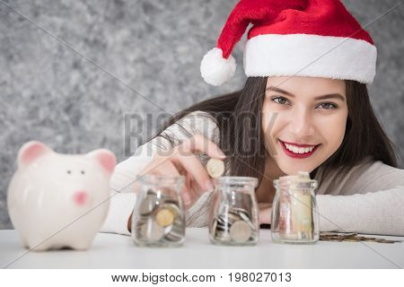 Beautiful young beautiful girl saving money for Christmas and holiday season. She is wearing a Santa hat saving money concept
