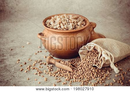 A small linen sack with raw buckwheat and a clay pot with hot buckwheat porridge on a gray background. Traditional Russian cuisine. The concept of a healthy diet. Toning of the image.