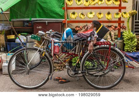 Yangon, Myanmar - September 26, 2016: An unidentified cycle rickshaw driver waits for tourists on the streets of Yangon in Myanmar.