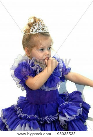 Little pageant girl fearfully sucks her thumb. She is wearing a tiara and wearing a fancy purple pageant dress.