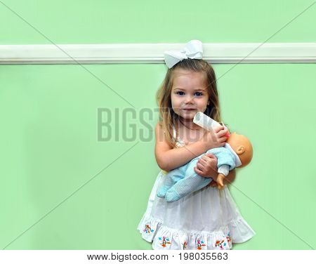 Little girl role plays as she pretends to feed her baby doll a bottle. She is standing in front of a green wall in her home.