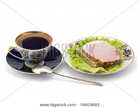 A Cup Of Coffee And A Plate With A Sandwich.