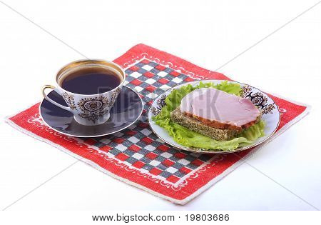 A Cup Of Coffee And A Plate With A Sandwich On A Red Napkin.