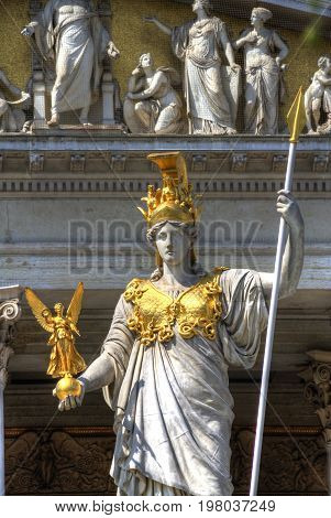 A statute of a women holding a spear with a golden angle and accents.