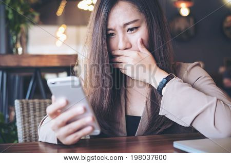 A beautiful Asian business woman looking at smart phone with feeling frightened in modern cafe