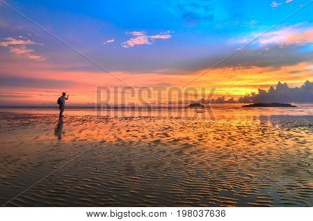 Man silhouette on the beautiful sunset on the beach at low tide & reflections in the sand.