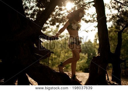 Beautiful little girl in costume of nymph dryad with floral head wreath stands on tree roots against sun in magical fairytale forest.