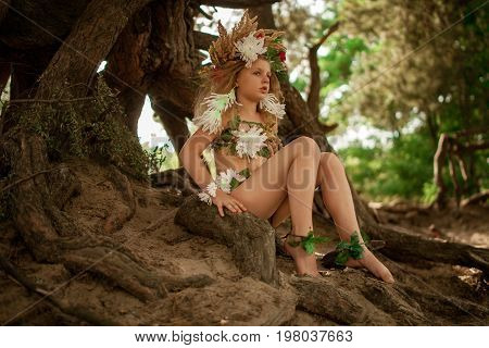 Beautiful little girl in image of nymph dryad with floral head wreath sits on tree roots in magical fairytale forest .