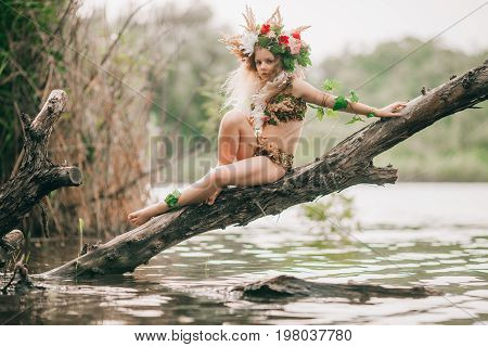 Beautiful little girl in image of nymph with floral head wreath sits on tree slanted above water.