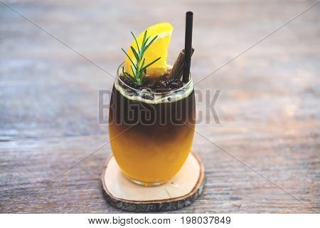 Closeup image of a glass of orange cold brew coffee on wooden table background