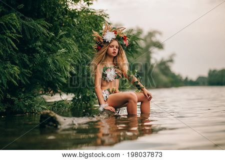 Beautiful little girl in image of nymph with floral head wreath sits on tree trunk in water. Her reflection is in water.