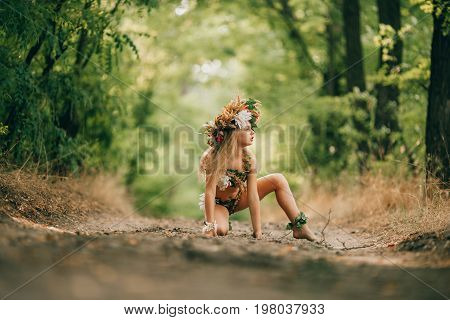 Beautiful little girl in image of nymph dryad with floral head wreath sits in forest road.