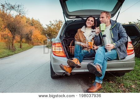 Tea party in car trunk - loving couple drinks hot tea from thermos flask sitting in car trunk