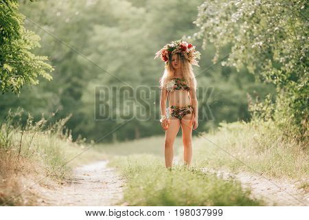Beautiful little girl in image of nymph dryad with floral head wreath stands in forest road. Close up.