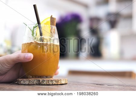 Closeup image of a woman's hand holding a glass of orange cold brew coffee on wooden table in cafe