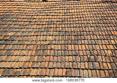 Vintage old roof covered with ceramic roof shingles of red color