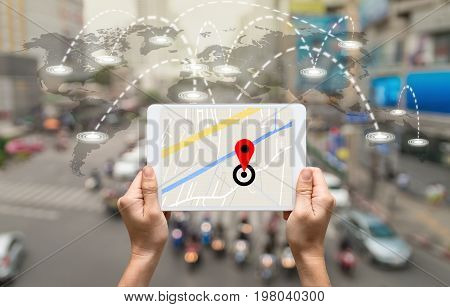 female hands holding a tablet showing part of navigator map on connection line over the world map with blurred photo of traffic jam Navigation conceptElements of this image furnished by NASA
