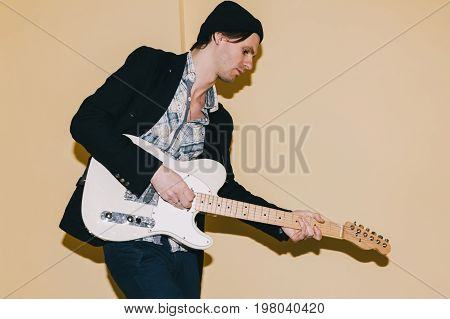 Guitarist thoughtfully playing guitar closeup. Music concert repetition, recording in studio