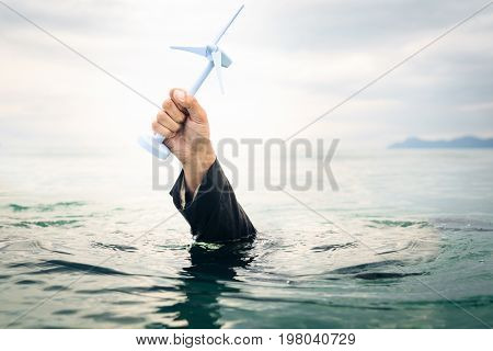 businessman holding a wind turbine above the water. concept for illustration the success - or failure - of off-shore wind power.