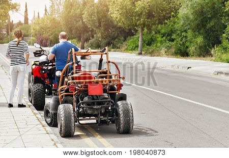 man and the woman are going on trip on Quad bikes on the road