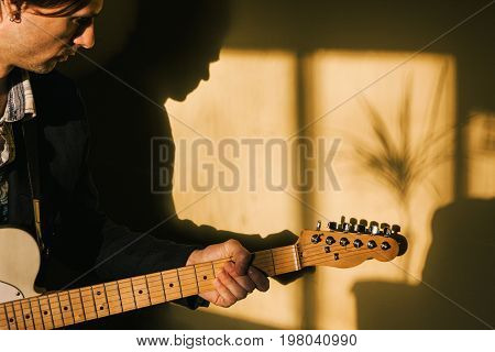 Guitarist with electric guitar playing at home. Adult male rehearsing at house, hobby for hipster, music concept
