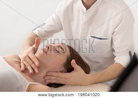 Closeup of masseur doing massage client. Doctor in the office doing massage young woman. master massage massaging his back to the client.