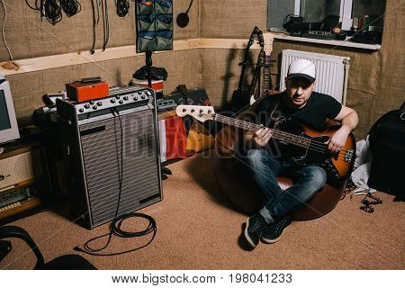 Guitarist in old garage music studio. Messy basement with instruments, album recording process