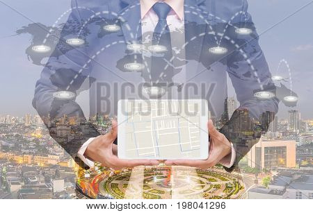 Businessman showing part of navigator map over the tablet screen on connection line over the world map with cityscape Navigation concept