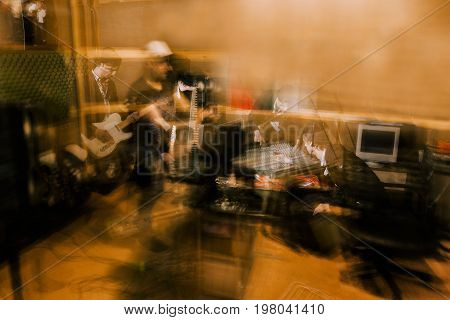 Musical recording studio in garage. Music background, band rehearsal before concert, unrecognizable musicians, blurred motion