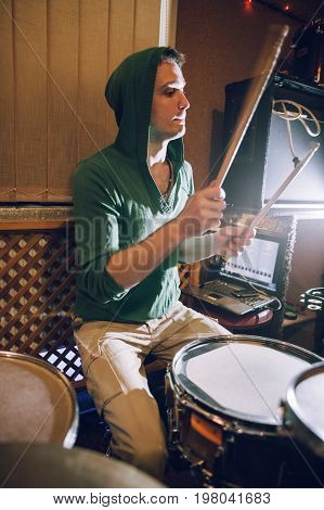 Male drummer playing drums in recording studio. Music band rehearsal before live concert