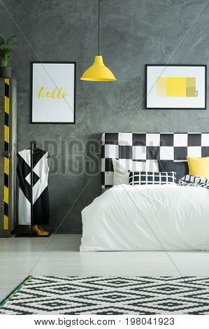 Two pictures above king-size bed in black and white bedroom with yellow elements