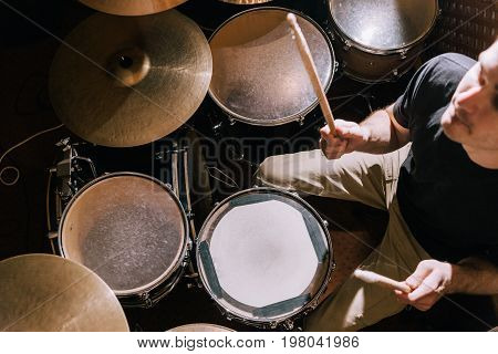 Drummer playing on drum kit top view. Live music concert, band recording process