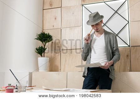 Designer thoughtfuly stands looking at paper. Young man considers on work results of designer sketch