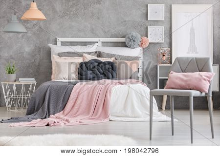 Gray chair with small pink pillow standing in a room with king-size bed
