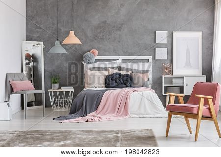 Two blankets in pastel colors falling off the wooden bed