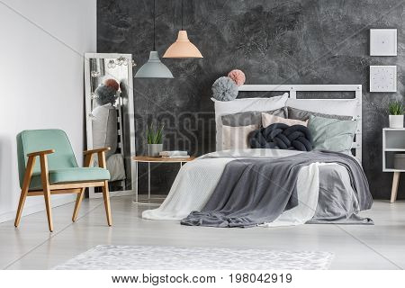 Comfy mint chair standing next to wooden bed with decorative cushion