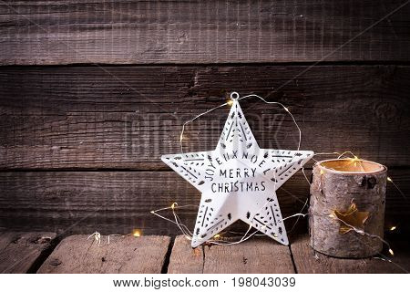 Christmas star candleholder and fairy light on aged wooden background. Decorative christmas composition. Place for text.