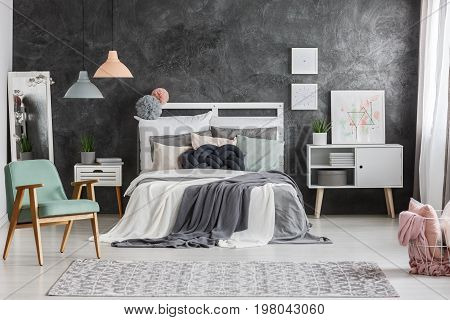 White cupboard with potted plant standing next to big bed with pillows
